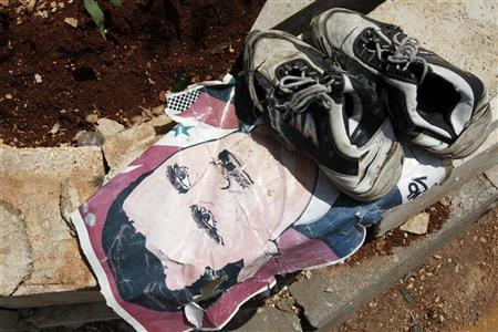 A portrait of Syrian President Bashar al-Assad lies under a pair of shoes at the Bab Al-Salam border crossing to Turkey August 1, 2012. REUTERS/Umit Bektas