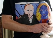 Организатор аукционных торгов Алексей Сергиенко держит яйцо, расписанное художником Дмитрием Шагиным, с лицами участниц группы Pussy Riot во время аукциона в Санкт-Петербурге, 15 апреля 2012 года. Прославившись на весь мир панк-молебном в главном российском храме, три участницы феминистской группы Pussy Riot предстали на этой неделе перед судом измученными, похудевшими и бледными. REUTERS/Alexander Demianchuk
