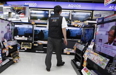 A salesperson walks among Sharp Corp's Aquos liquid-crystal display (LCD) televisions displayed at an electronic store in Tokyo in this June 8, 2012 file photograph. REUTERS/Toru Hanai/Files