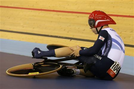 Britain's Philip Hindes sits on the ground as he waits for assistance after falling during their track cycling men's team sprint qualifying heats at the Velodrome during the London 2012 Olympic Games August 2, 2012. The officials had to assist Hindes as his left foot remained clipped in after the fall. REUTERS/Cathal McNaughton