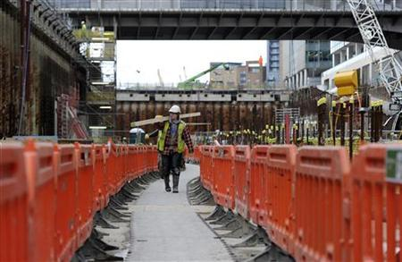 A worker walks at the construction site of the new Crossrail Station at Canary Wharf in London February 7, 2011. REUTERS/Paul Hackett