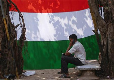 A man speaks on the phone outside his shanty in front of the national flag in Dharavi, one of Asia's largest slums, in Mumbai January 24, 2012. REUTERS/Danish Siddiqui/Files