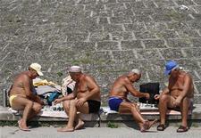 Мужчины играют в шахматы на пляже на берегу Днепра в Киеве, в то время как температура воздуха достигла 35 градусов по Цельсию 18 июля 2010 года. Рост украинской экономики замедлится в третьем квартале 2012 года до 0,9-1,0 процента с 6,5 процента в третьем квартале 2011 года из-за увеличившихся потерь урожая зерновых в условиях аномальной жары и сокращения инвестиций в период подготовки к назначенным на октябрь парламентским выборам, полагают участники ежемесячного опроса Рейте. REUTERS/Konstantin Chernichkin