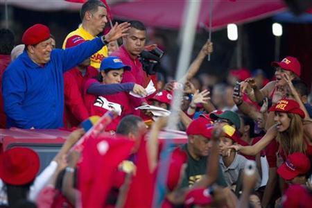 Venezuela's President Hugo Chavez (L) greets supporters during an election rally in the low income neighborhood of Petare in Caracas July 28, 2012. REUTERS/Carlos Garcia Rawlins