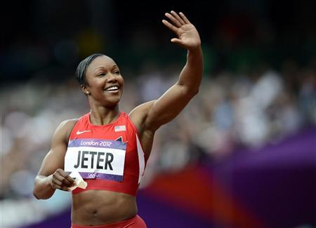 Carmelita Jeter of the U.S. waves as she celebrates after placing first in her women's 100m round 1 event at the London 2012 Olympic Games in the Olympic Stadium August 3, 2012. REUTERS/Dylan Martinez