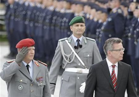German Defence Minister Thomas de Maiziere (R) and Chief of Staff of the German Military General Volker Wieker inspect the guard of honour during a ceremony for new recruits in Berlin July 20, 2012. REUTERS/Tobias Schwarz