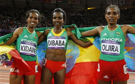 Ethiopia's Tirunesh Dibaba smiles after her gold medal win as she poses with compatriots Werknesh Kidane (L) and Beleynesh Oljira (R) at the women's 10,000m final at the London 2012 Olympic Games at the Olympic Stadium August 3, 2012. Kidane placed fourth and Oljira placed fifth. REUTERS/Phil Noble