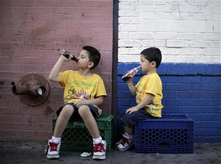 Children drink soda as they sit in the shade on a hot day in downtown Los Angeles April 8, 2010. REUTERS/Lucy Nicholson