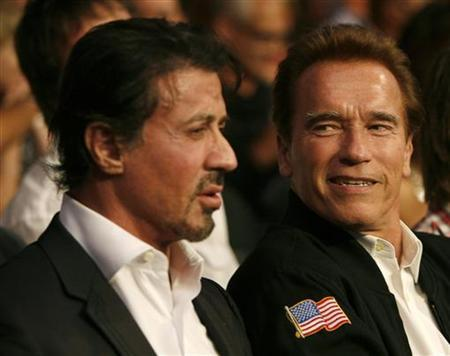 Sylvester Stallone (L) and Arnold Schwarzenegger wait for the start of the WBC Heavyweight Championship boxing bout between Vitali Klitschko of Ukraine and Cristobal Arreola of the U.S. at the Staples Center in Los Angeles, California September 26, 2009. REUTERS/Mike Blake