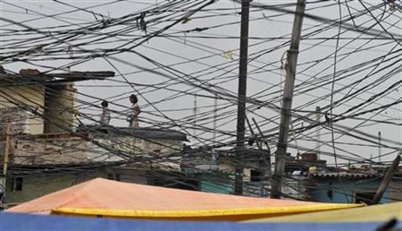 Tangled overhead electric power cables are pictured at a residential area as children stand on the roof of a house in Noida on the outskirts of New Delhi August 1, 2012. REUTERS/Parivartan Sharma/Files