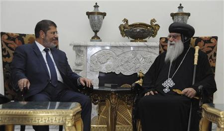 The Muslim Brotherhood's President-elect Mohamed Mursi (L) meets with Egyptian Coptic Bishop Bakhomious at his office in the Presidency, in Cairo June 26, 2012. REUTERS/Middle East News Agency (MENA)/Handout