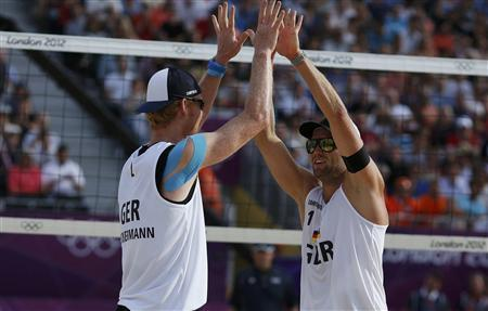 Germany's Jonas Reckermann (L) and Julius Brink celebrate after defeating Latvia's Aleksandrs Samoilovs and Ruslans Sorokins during their men's round of 16 beach volleyball match at Horse Guards Parade during the London 2012 Olympic Games August 4, 2012. REUTERS/Marcelo del Pozo