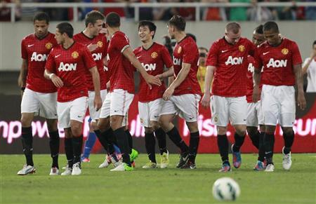 Manchester United's players celebrate after their teammate Shinji Kagawa (centre L) scored a goal during a friendly soccer match against Shanghai Shenhua at the Shanghai Stadium in Shanghai, July 25, 2012. REUTERS/Aly Song