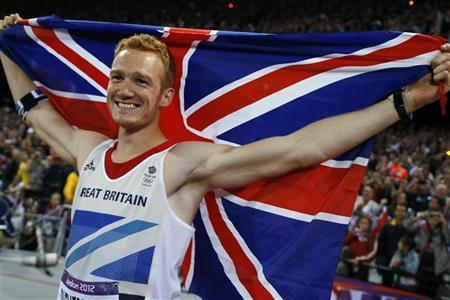 Britain's Greg Rutherford holds the Union Flag after winning the gold in the men's long jump final at the London 2012 Olympic Games at the Olympic Stadium August 4, 2012. REUTERS/Phil Noble