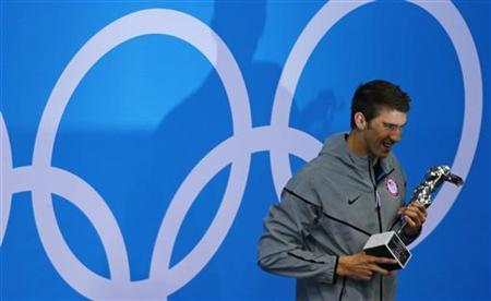 Michael Phelps of the U.S. poses with his trophy awarded to him by FINA honouring him as the most decorated Olympian of all time, after winning the men's 4x100m medley relay final during the London 2012 Olympic Games at the Aquatics Centre August 4, 2012. Phelps ended his incredible Olympic career on the perfect note on Saturday, winning his 18th gold medal for the United States in the men's medley relay, the last time he will swim a competitive race. The trophy reads, ''To Michael Phelps, the greatest Olympic athlete of all time, from FINA''. REUTERS/Brian Snyder