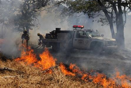 Firefighters battle a wildfire near the town of Noble in Cleveland County, south of Oklahoma City, Oklahoma, August 4, 2012. REUTERS/Garett Fisbeck