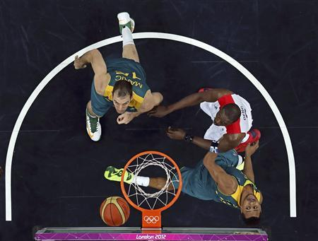 Australia's Patrick Mills (R) watches his shot with teammate Australia's Aleks Maric (L) and Great Britain's Luol Deng (C) during their men's preliminary round Group B basketball match at the Basketball Arena during the London 2012 Olympic Games August 4, 2012. REUTERS/Mike Segar