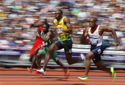Usain Bolt (C) of Jamaica runs on his way to winning his 100m heat round 1 during the London 2012 Olympic Games at the Olympic Stadium August 4, 2012. REUTERS/Phil Noble