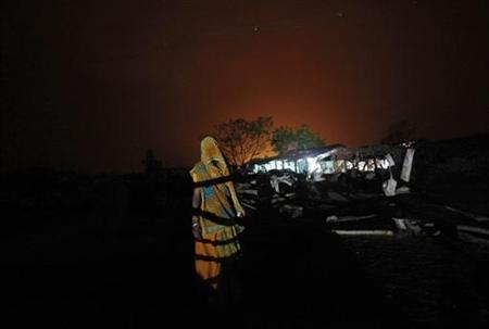 A woman stands in front of an illuminated house powered by solar energy at Meerwada village of Guna district in Madhya Pradesh June 18, 2012. REUTERS/Adnan Abidi/Files