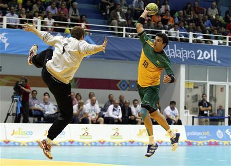 Felipe Ribeiro (R) of Brazil scores against goalkeeper Carlos Matias Schulz of Argentina during the men's handball gold medal match at the Pan American Games in Guadalajara October 24, 2011. REUTERS/Sergio Moraes