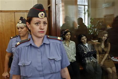 Nadezhda Tolokonnikova (3rd R), Yekaterina Samutsevich (2nd R) and Maria Alyokhina (R), members of female punk band ''Pussy Riot'', attend their trial inside the defendant's cell in a court in Moscow August 3, 2012. President Vladimir Putin said on Thursday that three women on trial for a protest performance in Russia's main cathedral should not be judged too harshly, signaling he did not favor lengthy prison terms for the Pussy Riot band members, Russian news agencies reported. REUTERS/Maxim Shemetov