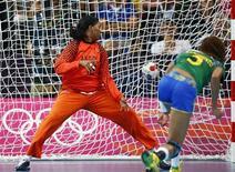 A brasileira Alexandra Nascimento marca um gol contra a goleira angolana Cristina Direito numa partida de handebol nos Jogos Olímpicos de 2012 em Londres, no Reino Unido. 5/08/2012 REUTERS/Marko Djurica