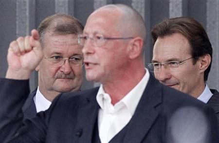Outgoing CEO of Porsche Wendelin Wiedeking (L) and his successer Michael Macht (R) listen to Uwe Hueck emplyee spokesman giving a statement during an employee meeting at Porsche headquarters in Stuttgart July 23, 2009. SREUTERS/Johannes Eisele