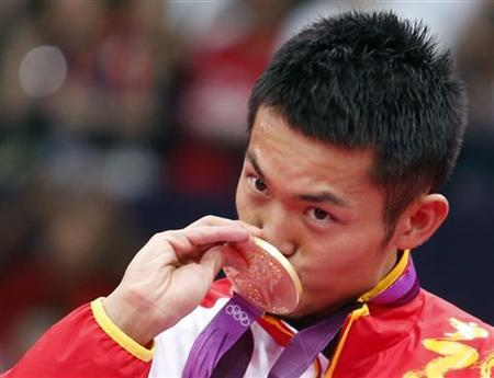 China's Lin Dan kisses his gold medal at the victory ceremony for the men's singles badminton event at the London 2012 Olympic Games at the Wembley Arena August 5, 2012. REUTERS/Bazuki Muhammad