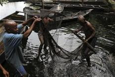 Fishermen sort out their fishing net at the bank of a polluted river in Bidere community in Ogoniland in Nigeria's delta region August 20, 2011. Picture taken August 20, 2011. REUTERS/Akintunde Akinleye