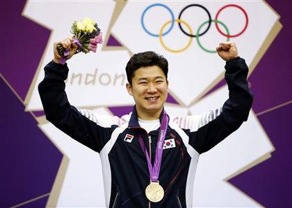 South Korea's Jin Jongoh on the podium after winning gold during the men's 50m pistol victory ceremony at the Royal Artillery Barracks during the London 2012 Olympic Games August 5, 2012. REUTERS/Jorge Silva