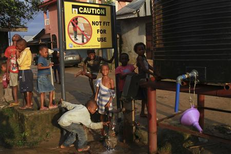 Children play near a borehole where a signboard is erected in Eleme community, outside Nigeria's oil hub city of Port Harcourt August 1, 2012. A bright yellow sign above the well in this sleepy Nigerian village says 'caution: not fit for use', and the sulphurous stink off the water that children still pump into buckets sharply reinforces that warning. Prosperity has flowed from Ogoniland, one of Africa's earliest crude oil producing areas, for decades. But it has flowed to the big oil companies and to Nigerian state coffers. Locals have long complained that precious little goes their way. To match Insight NIGERIA-OILPOLLUTION/ Picture taken August 1, 2012. REUTERS/Akintunde Akinleye