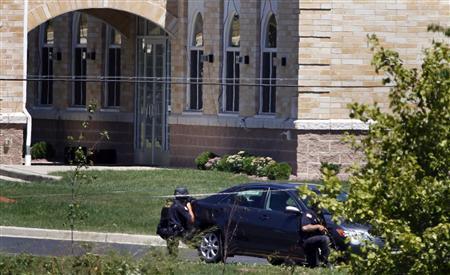 Police officer take cover outside the Sikh Temple in Oak Creek, Wisconsin August 5, 2012 following a mass shooting inside and outside the Sikh Temple. REUTERS-Allen Fredrickson