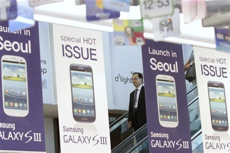 A man standing on an escalator passes Samsung Electronics' new Galaxy S III smartphone advertisement boards at a Samsung Electronics store in the company's main office building in Seoul July 27, 2012. REUTERS/Kim Hong-Ji