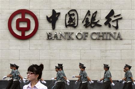 A woman stands on a street as security guards march behind her outside the Bank of China headquarters in the financial district of Beijing in this August 19, 2009 file photograph. REUTERS/David Gray/Files