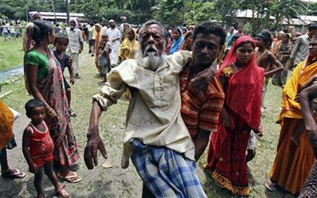Jahar (C), a 105-year-old villager affected by ethnic riots, is carried by his son to a relief camp near Bijni town in the northeastern Indian state of Assam July 26, 2012. REUTERS/Utpal Baruah
