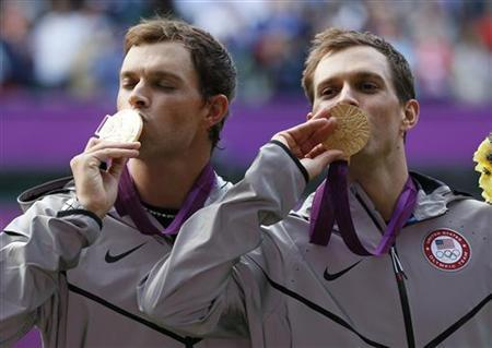 Brothers Bob Bryan (R) and Mike Bryan of the U.S. kiss their gold medals during the presentation ceremony after they defeated France's Jo-Wilfried Tsonga and Michael Llodra in the men's doubles tennis final match at the All England Lawn Tennis Club during the London 2012 Olympic Games August 4, 2012. REUTERS/Stefan Wermuth