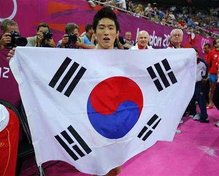 Yang Hak Seon of South Korea holds his flag as he celebrates winning a gold medal in the men's gymnastics vault final in the North Greenwich Arena during the London 2012 Olympic Games August 6, 2012. REUTERS/Mike Blake