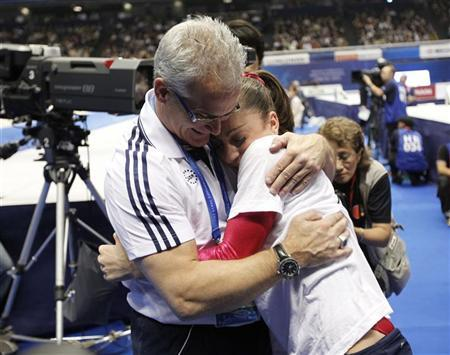 Jordyn Wieber (L) of the U.S. hugs with her head Coach John Geddert after winning the women's individual all-around final at the Artistic Gymnastics World Championships in Tokyo October 13, 2011. REUTERS/Kim Kyung-Hoon