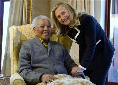 U.S. Secretary of State Hillary Rodham Clinton poses for a photograph with Nelson Mandela, former president of South Africa, at his home in Qunu, August 6, 2012. REUTERS/Jacquelyn Martin/Pool