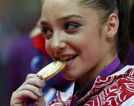 Aliya Mustafina of Russia bites her gold medal during the women's gymnastics asymmetric bars victory ceremony in the North Greenwich Arena during the London 2012 Olympic Games August 6, 2012.REUTERS/Brian Snyder