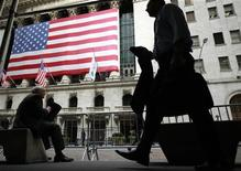 Morning commuters are seen outside the New York Stock Exchange, July 30, 2012. REUTERS/Brendan McDermid