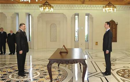 Riyad Hijab is sworn in as new Prime Minister by Syrian President Bashar al-Assad (R) in Damascus in this handout photo distributed by Syrian News Agency (SANA) June 26, 2012. REUTERS/SANA/Handout