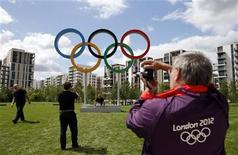 A volunteer takes a photograph of the Olympic rings at the Athletes' Village at the Olympic Park in London, July 19, 2012. REUTERS/Jae C. Hong/Pool