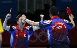 South Korea's Ryu Seungmin (L) celebrates with Oh Sangeun after defeating Hong Kong's Jiang Tianyi and Leung Chu Yan in their men's team semifinals table tennis doubles match at the ExCel venue during the London 2012 Olympic Games August 6, 2012. REUTERS/Darren Staples