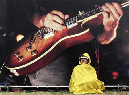 A Chinese rock fan sits in front of a Gibson guitar poster during the four-day MIDI Music Festival at Haidian Park in Beijing May 4, 2006 as the week-long Labour Day holidays continue. REUTERS/Claro Cortes