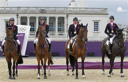 Britain's equestrian team jumping members sit on their horses with their gold medals in Greenwich Park at the London 2012 Olympic Games August 6, 2012. REUTERS/Mike Hutchings