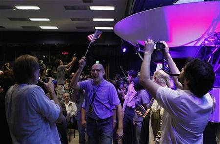 Mars Science Laboratory Curiosity rover team member Miguel San Martin (C) waves an American flag after a successful rover landing, as he arrives for a news conference at NASA's Jet Propulsion Lab in Pasadena, California August 5, 2012. REUTERS/Fred Prouser