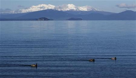 The volcanic peaks of Mounts Tongariro, Ngarruhoe and Ruapehu rise over the shores of Lake Taupo September 28, 2011. REUTERS/Mike Hutchings