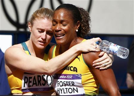 Australia's Sally Pearson (L) consoles Jamaica's Brigitte Foster-Hylton after she failed to advance from her round 1 women's 100m hurdles heat during the London 2012 Olympic Games at the Olympic Stadium August 6, 2012. REUTERS/David Gray