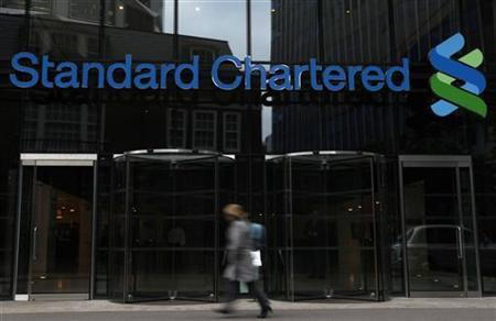 A woman walks past a Standard Chartered bank in London October 13, 2010. REUTERS/Stefan Wermuth/Files